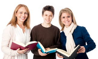 Two women and one young man looking up with open books in their hands.